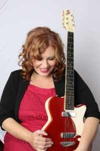 A woman with reddish hair holding a guitar